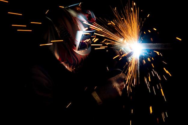 金属溶接を実行するマスクの男性溶接機。濃い色の写真。飛ぶ火花。 Premium写真