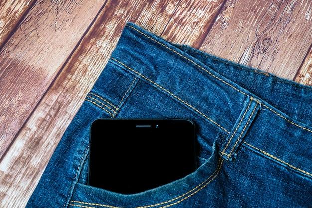 Черный смартфон торчит из кармана джинсов Premium Фотографии