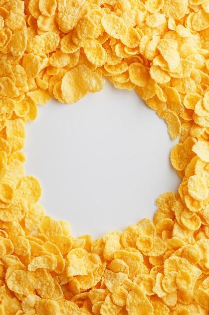 空のホワイトスペースを持つ完全なフレームに黄金のコーンフレーク。健康的な朝食 Premium写真