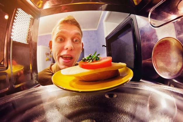 幸せな男がサンドイッチを電子レンジに入れる Premium写真
