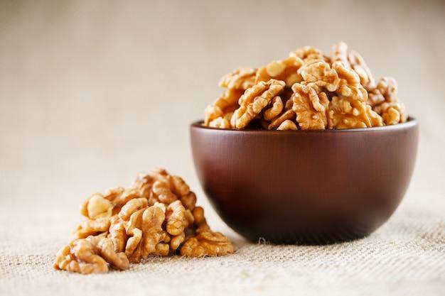 Очищенные грецкие орехи в деревянной, темно-коричневой чашке на ткани мешковины. Premium Фотографии
