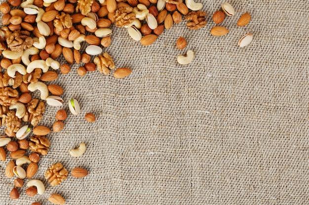 黄麻布の生地に対して木製カップで異なるナッツを混ぜます。構造および背景、マクロとしてのナット。上面図。 Premium写真