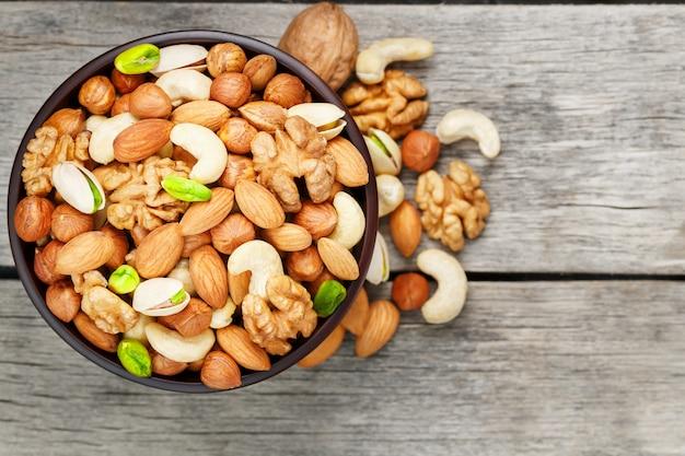 木製グレーのミックスナッツと木製ボウル。クルミ、ピスタチオ、アーモンド、ヘーゼルナッツ、カシューナッツ、クルミ。 Premium写真