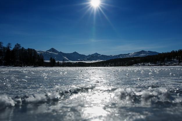 氷と雪で覆われた凍った湖のパノラマ。晴天の日差しの中で青い空。アルタイ。 Premium写真