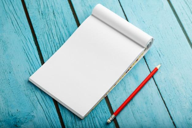教育のため、青い木製のテーブル背景に赤鉛筆でメモ帳を書く目標と行為 Premium写真