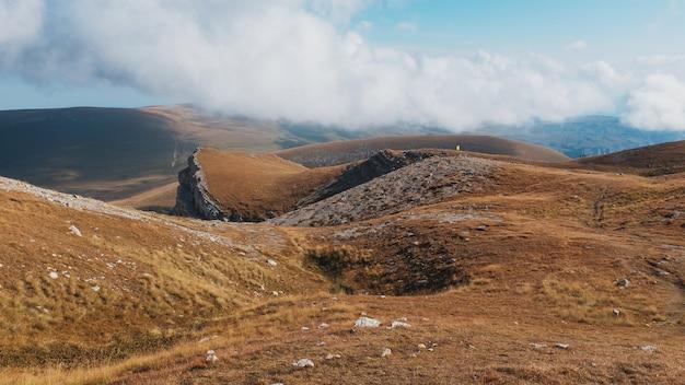 遠くに観光客や旅行者がいる雄大な風景を通る山頂や丘を通るルート。 Premium写真