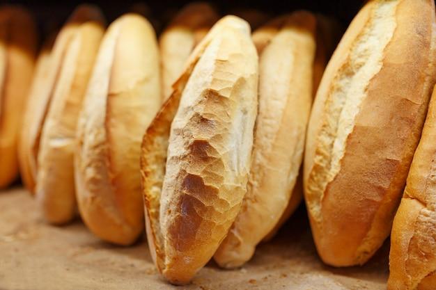 Свежеиспеченный ароматный и свежий хлеб из пекарни лежит и хранится на прилавке для продажи. Premium Фотографии