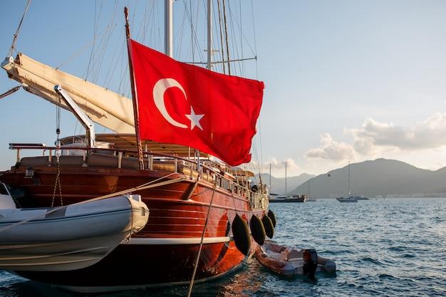 桟橋にトルコの大きな旗を持つ美しい木製ヨット Premium写真
