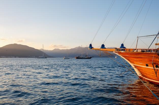 木漏れ日と美しい夕焼け空を背景に桟橋にヨット Premium写真