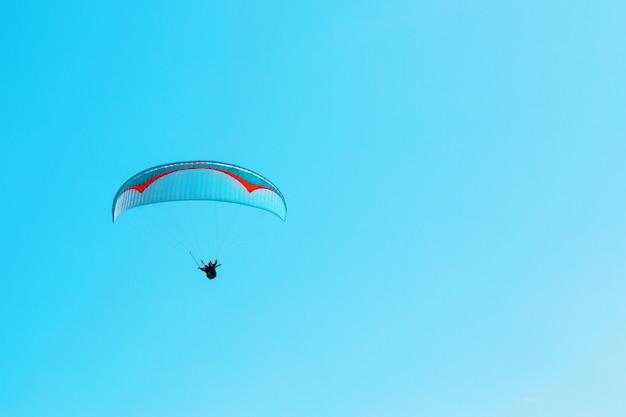Параплан взлетает на фоне голубого неба с чистым пространством Premium Фотографии