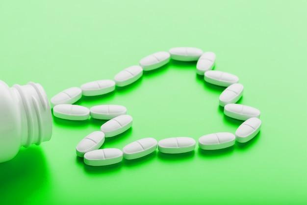 グリーンの白い瓶からこぼれた歯の形のカルシウムビタミン。 Premium写真