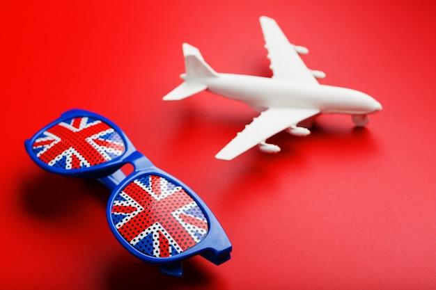 白い旅客機は、イギリスの国旗とサングラスで飛ぶ。 Premium写真