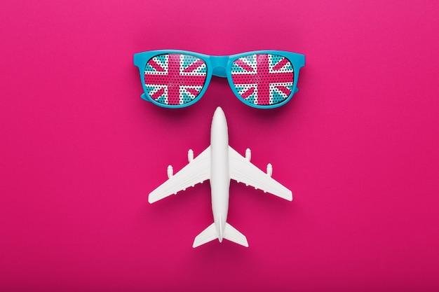 白い飛行機とクレイジーピンクの表面上のレンズにイギリス国旗のターコイズサングラス Premium写真