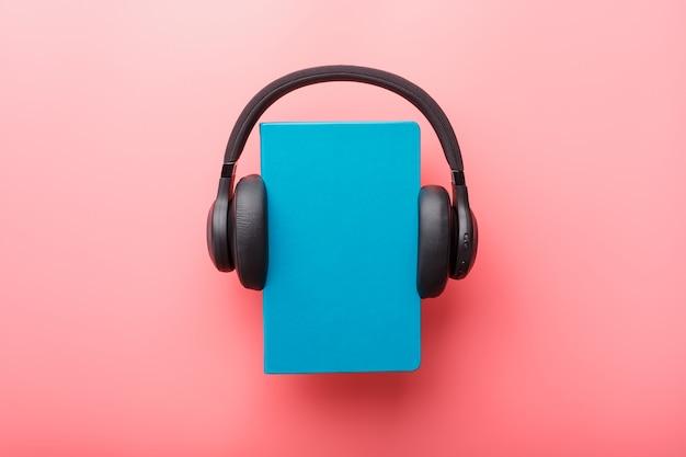 ヘッドフォンは、ピンクの背景、上面の青いハードカバーの本に着用されています。 Premium写真