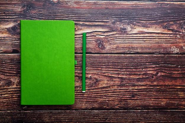 Зеленый блокнот с фломастером на коричневом деревянном столе, вид сверху. Premium Фотографии
