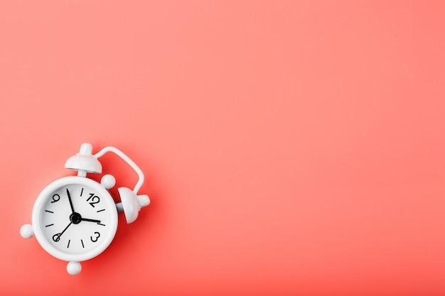 Белый ретро будильник на розовом фоне. понятие времени со свободным пространством для текста. Premium Фотографии