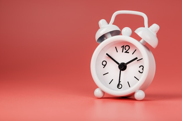 ピンクの背景に白のレトロな目覚まし時計。テキスト用の空き容量のある時間の概念。 Premium写真
