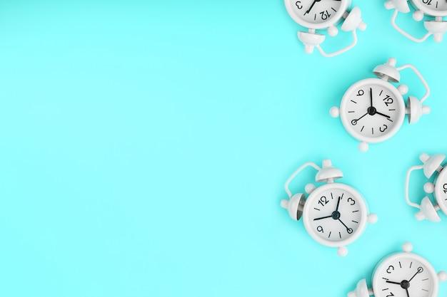 青色の背景にパターンの形で多くの白い古典的な目覚まし時計のパターン。スペースのコピーを含む平面図、フラットレイ。 Premium写真