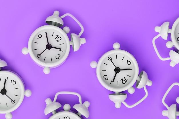 紫色の背景にパターンの形で多くの白い古典的な目覚まし時計のパターン。スペースのコピーを含む平面図、フラットレイ。 Premium写真