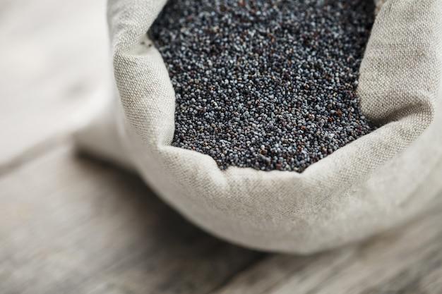 黄麻布の袋にケシの実。たんぱく質と油分が豊富でおいしい有用な種子。 Premium写真