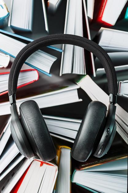 ワイヤレスオーバーヘッドブラックヘッドフォンは本の上にあります。オーディオブックを通して学ぶという概念。本を聞くこと。 Premium写真