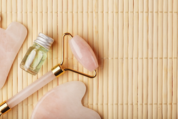 天然ローズクォーツで作られた顔のマッサージ技術グアシャのためのツールのセット。ローラー、ヒスイの石、ガラスの瓶の中の油、顔と体のケアのためのストロー背景に。 Premium写真