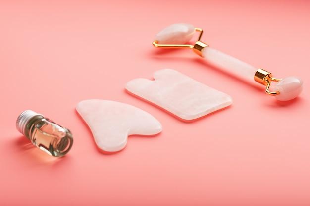 顔と体のケアのためのピンクの背景に天然ピンクのクォーツローラー、ヒスイの石、オイルで作られたグアシャマッサージツール。漢方薬の一部 Premium写真