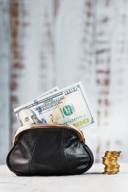 Кошелек с деньгами на серую стену. сохранение бюджета и сохранение вашей мечты. Premium Фотографии