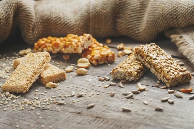 Ассорти козинаки ,, с мешковиной ткани. стиль кантри. вкусные сладости из семян подсолнечника, кунжута и арахиса, покрытые блестящей глазурью. Premium Фотографии