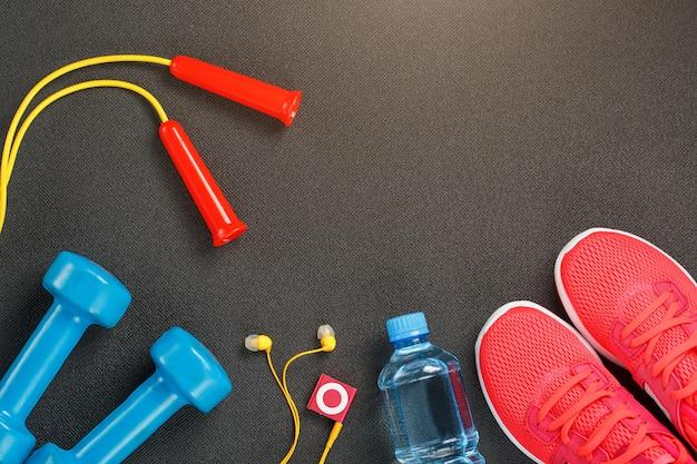 スポーツ用品、ダンベル、縄跳び、ボトル入り飲料水、スニーカー、プレーヤーのトップビュー Premium写真