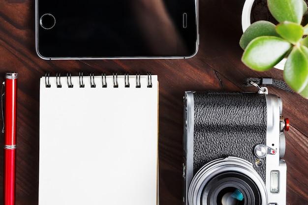 空白のメモ帳ページと暗い茶色の木製のテーブル、電話と緑の花を持つヴィンテージのテーブルに赤ペンで古典的なカメラ Premium写真
