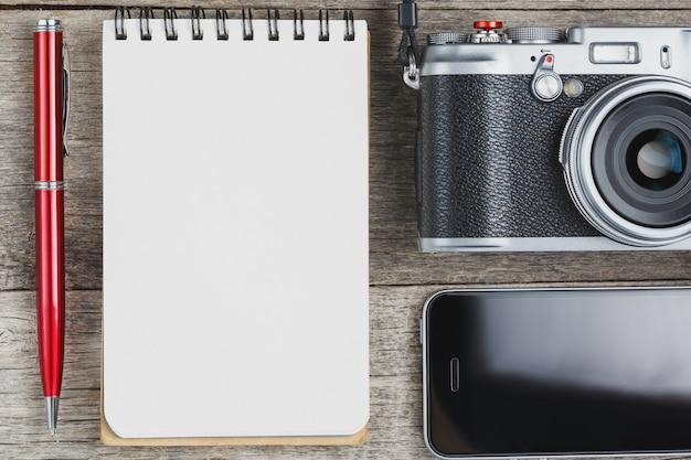 空白のメモ帳ページと電話付きの灰色の木製、ビンテージデスクに赤ペンでクラシックカメラ。 Premium写真