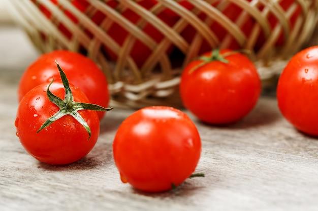 古い木製のテーブルの枝編み細工品バスケットで新鮮な赤いトマト。黄麻布の周りの水分、灰色の木製テーブルの滴と熟したジューシーなチェリートマト。素朴なスタイルで。 Premium写真