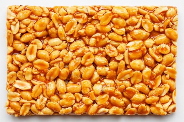 Большая плитка из жареного арахиса в сладкой патоке. козинаки полезные и вкусные сладости востока Premium Фотографии
