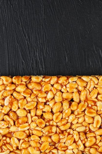 ピーナッツの大きな金色のタイル、甘い糖蜜のバー。東の便利でおいしいお菓子 Premium写真