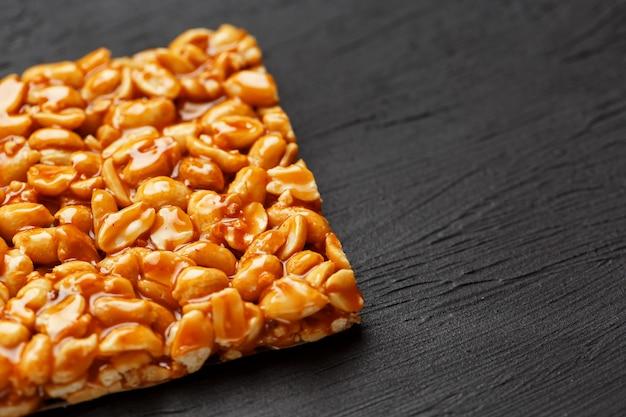 Большая золотая плитка из арахиса, батончик в сладкой патоке. козинаки полезные и вкусные сладости востока Premium Фотографии