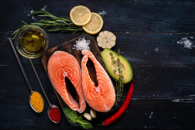 生の新鮮なサーモンステーキ、ハーブ、アボカド、バジル、レモン、ニンニク Premium写真