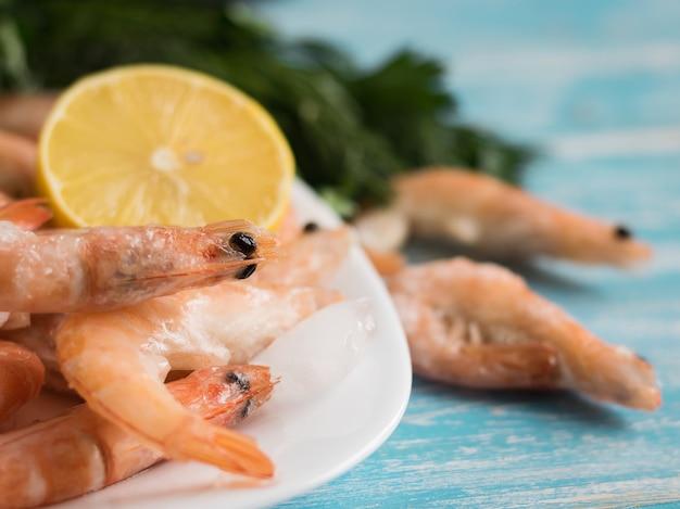 木製テーブルの上のレモンとパセリと陶器の白いボウルで冷凍エビ。 Premium写真