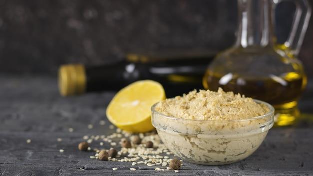 Свежая паста тахини из кунжутных семян с оливковым маслом и лимонным соком. Premium Фотографии