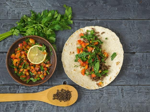 暗い木製のテーブルでメキシコのタコス、ベジタリアンサラダ、スパイスを調理するトルティーヤ Premium写真