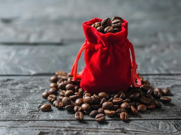 暗い木製のテーブルでローストコーヒー豆の赤いバッグ Premium写真