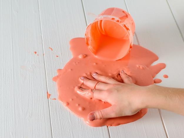 Руки ребенка размазаны по белому столу оранжевой улыбкой. Premium Фотографии