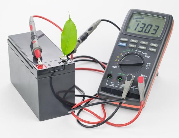 測定器と緑の葉が接続された充電式バッテリー。 Premium写真