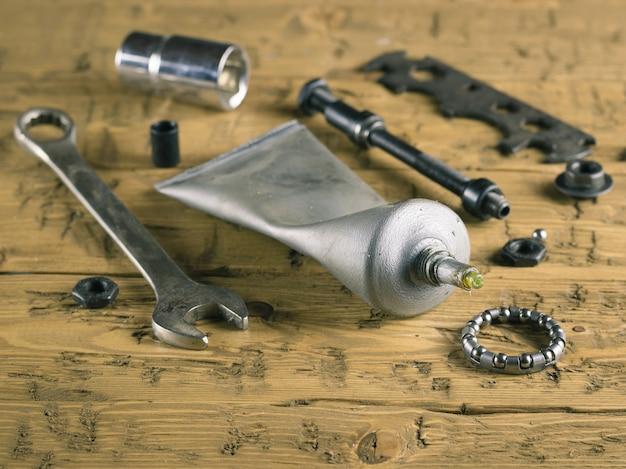 木製のテーブルの自転車修理用ツールとグリース。 Premium写真