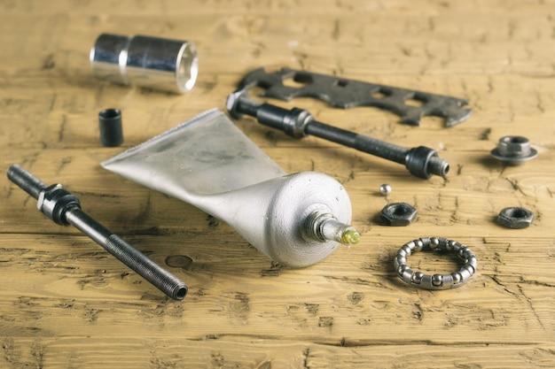 木製テーブルの上のツールと自転車の潤滑剤。 Premium写真