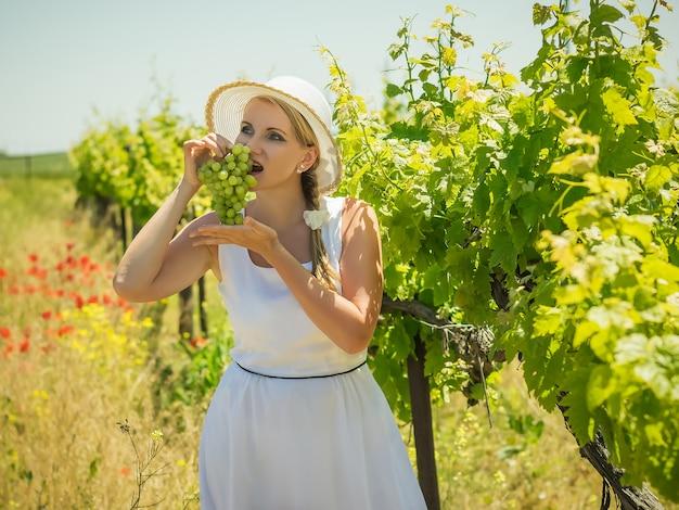 大きな白い帽子の女性は、フィールドで緑のブドウを食べます。 Premium写真