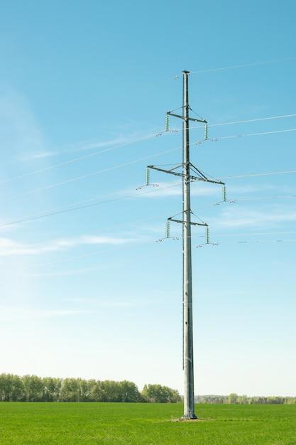 Железные подшипники высоковольтных линий электропередач на зеленом поле. Premium Фотографии