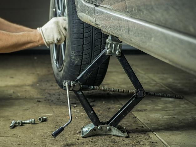 車の後輪の修理に手袋をした男。 Premium写真