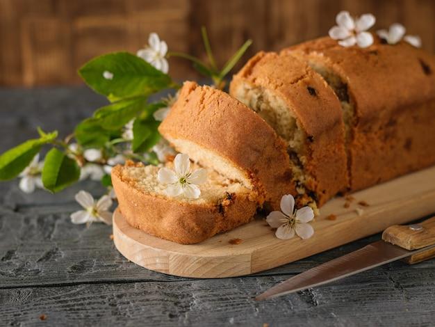 木製のテーブルにレーズンと開花小枝のケーキをスライスしました。 Premium写真