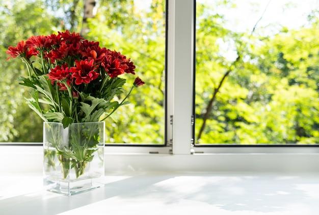 窓は赤い菊の花瓶です。 Premium写真
